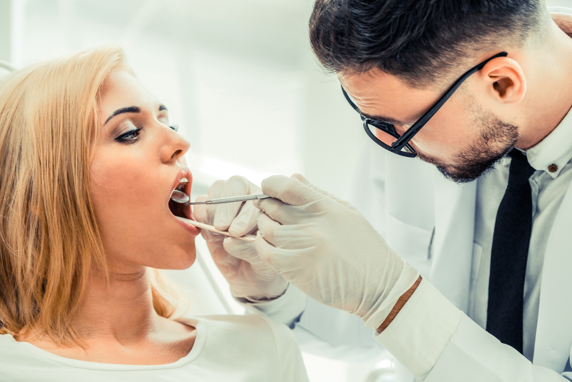 Young dentist examining patient in dental clinic.
