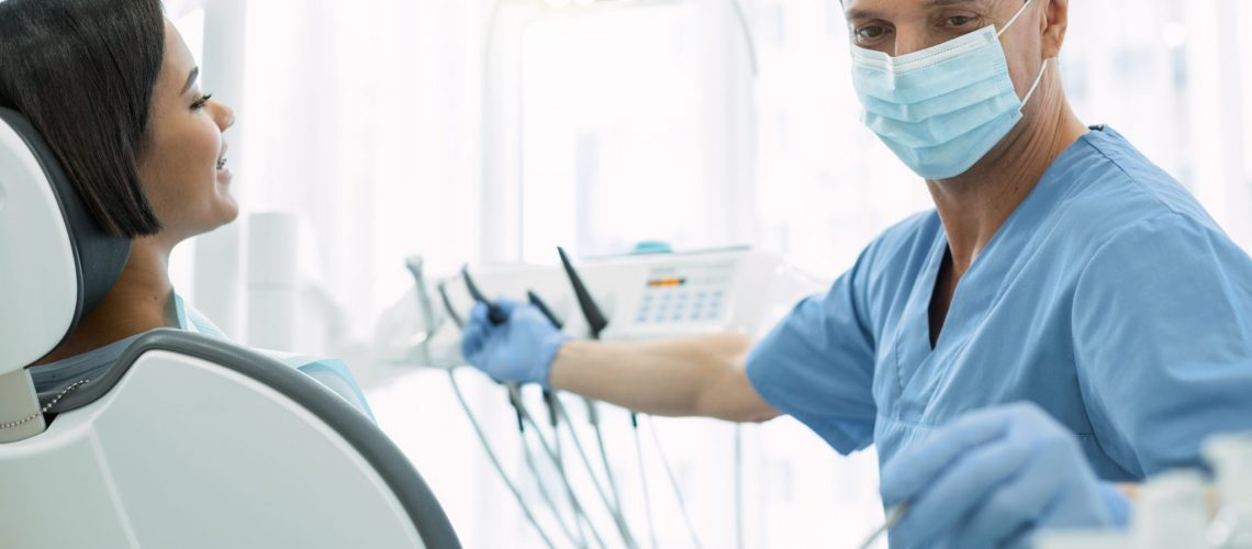 Serious male dentist holding an instrument